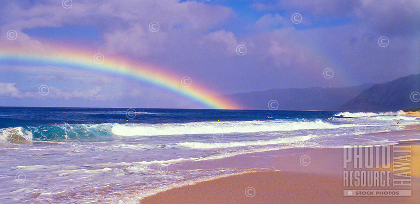 View of a rainbow over the water from a beautiful beach on the west side of Oahu