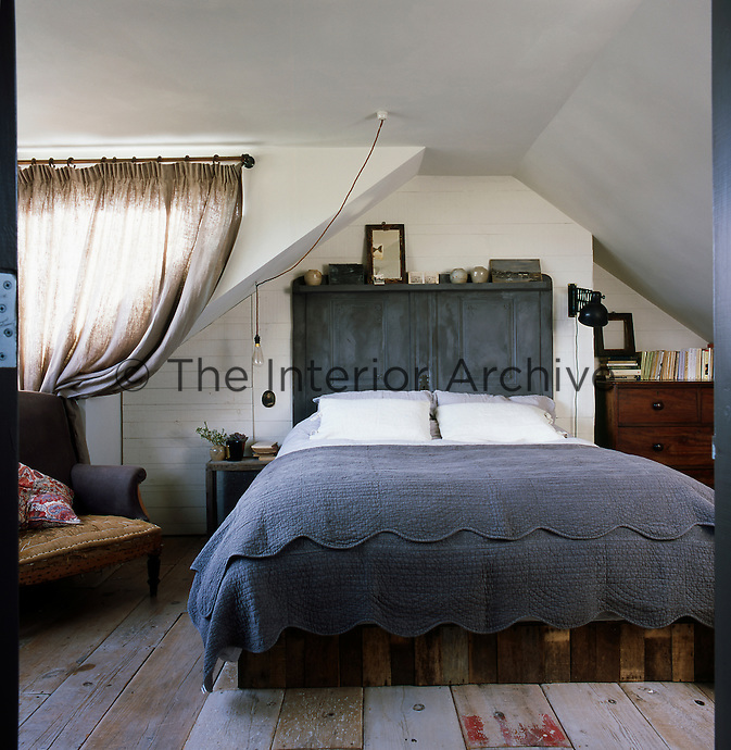 An attic bedroom with a double bed with a base made from timber and the box frame clad in crate wood. The curtains are made from Swedish linen and hang from poles made of copper piping. An antique French chair sits in front of a back wall clad with timber off-cuts to 'age' the loft extension. The bedroom has an interesting mix of antique pieces and reclaimed and recycled materials.