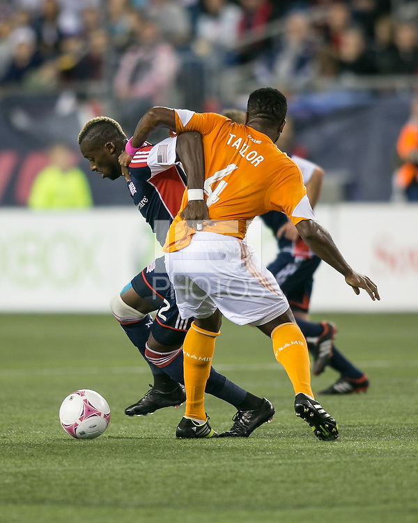 New England Revolution forward Dimitry Imbongo Boele (92) and Houston Dynamo defender Jermaine Taylor (4) compete for the ball.  The New England Revolution played to a 1-1 draw against the Houston Dynamo during a Major League Soccer (MLS) match at Gillette Stadium in Foxborough, MA on September 28, 2013.