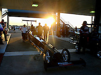 Oct 16, 2015; Ennis, TX, USA; The sun sets as crew members push NHRA top alcohol dragster driver James Thompson towards the starting line during qualifying for the Fall Nationals at the Texas Motorplex.. Mandatory Credit: Mark J. Rebilas-USA TODAY Sports