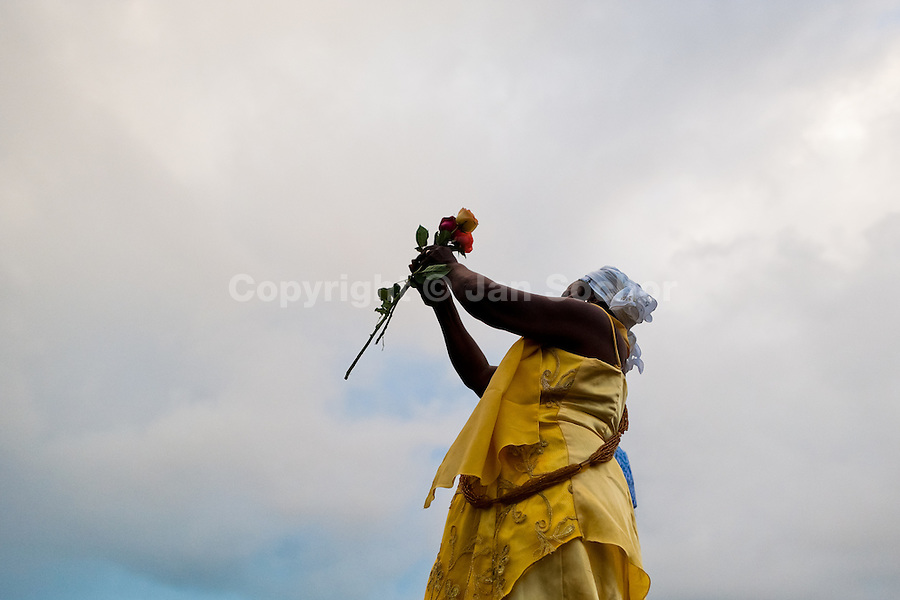 A Baiana woman throws flowers in the sea during the celebration of Yemanjá, the goddess of the sea, in Salvador, Bahia, Brazil, 2 February 2012. Yemanjá, originally from the ancient Yoruba mythology, is one of the most popular ?orixás?, the deities from the Afro-Brazilian religion of Candomblé. Every year on February 2nd, thousands of Yemanjá devotees participate in a colorful celebration in her honor. Faithful, usually dressed in the traditional white, gather on the beach at dawn to leave offerings for their goddess. Gifts for Yemanjá include flowers, perfumes or jewelry. Dancing in the circle and singing ancestral Yoruba prayers, sometimes the followers enter into a trance and become possessed by the spirits. Although Yemanjá is widely worshipped throughout Latin America, including south of Brazil, Uruguay, Cuba or Haiti, the most popular cult is maintained in Bahia, Brazil.
