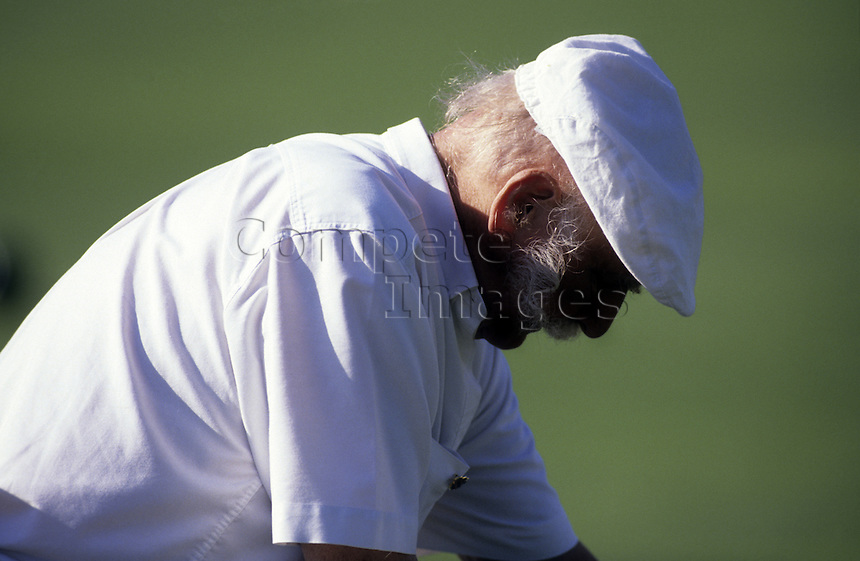 Elderly man taking a break from lawn bowls