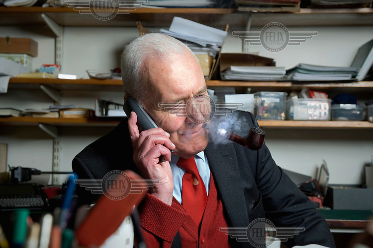 Tony Benn, a left-wing former MP and Minister in successive Labour Party governments. Photographed talking on a phone and smoking his pipe in the study of his home in Holland Park, West London..