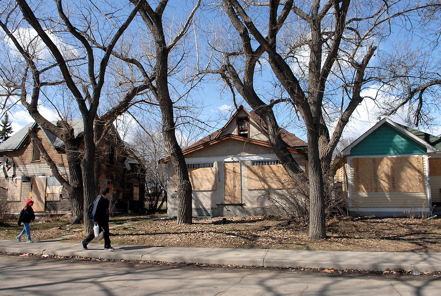 A man and a child walk past a row of boarded up homes in North Central Regina. MARK TAYLOR GALLERY