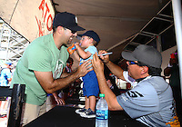 Jul. 25, 2014; Sonoma, CA, USA; A young fan gets an autograph from NHRA funny car driver Cruz Pedregon at the Toyota Pit Pass display during qualifying for the Sonoma Nationals at Sonoma Raceway. Mandatory Credit: Mark J. Rebilas-