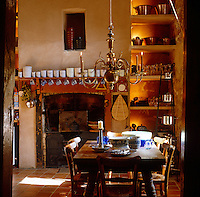 A warm afternoon glow in the rustic kitchen with a brass chandelier hanging over the wooden table