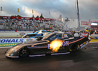 Feb 7, 2014; Pomona, CA, USA; NHRA funny car driver Alexis DeJoria (near lane) races alongside Jeff Diehl during qualifying for the Winternationals at Auto Club Raceway at Pomona. Mandatory Credit: Mark J. Rebilas-