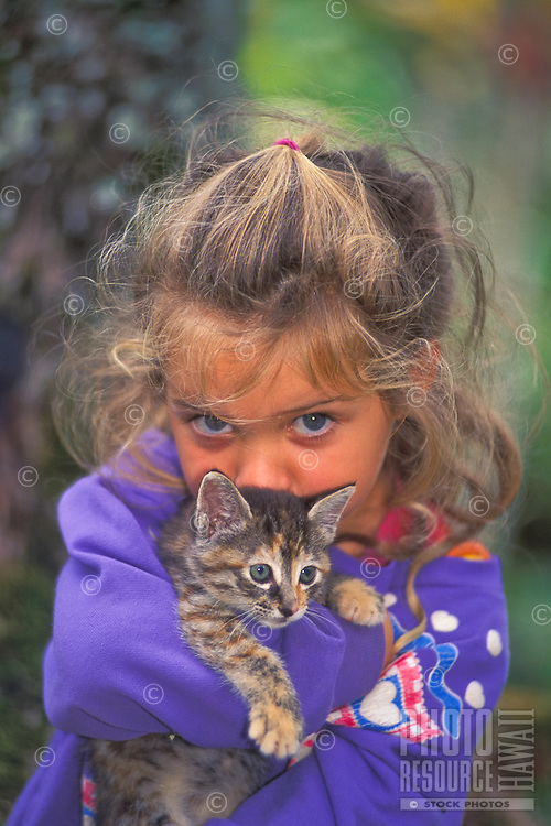 Young girl lovingly holding small kitten