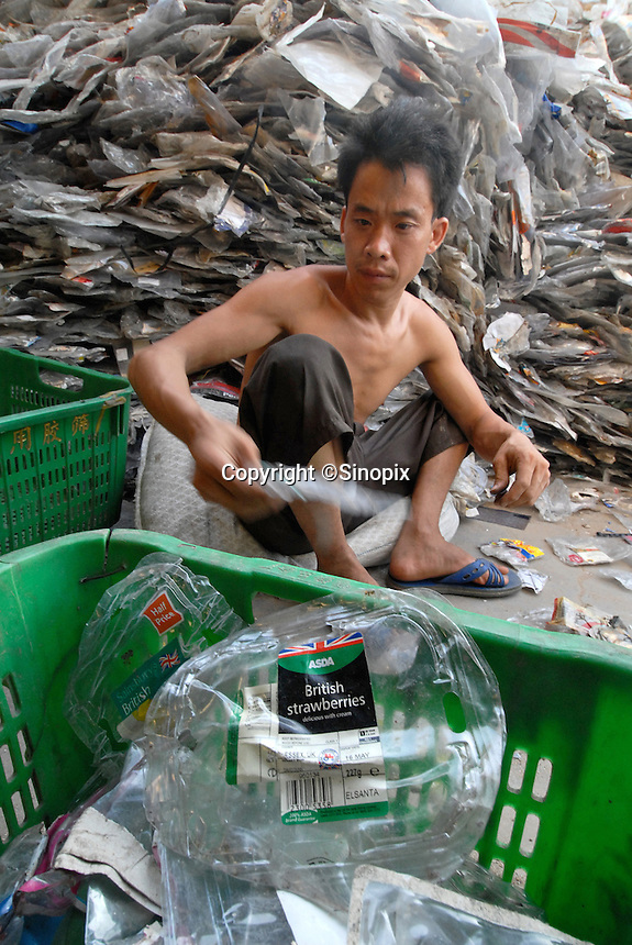 Migrant worker sorts through waste plastic from British supermarkets in a trash town in China. Lian Jiao town near Nanhai in China's Guangdong Province is a heavily polluted township that recycles waste plastic much of which is brought from European countries. All of the plastic here comes from the UK..30 Aug 2006