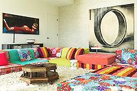 The living room doubles as a sleeping area with funky colourful modular sofas