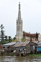 Shacks and 19th Century Catholic cathedral on the Mekong River, Cai Be, Tien Giang Province, Vietnam