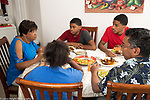 Dominican American family sitting at dinner table, eating traditional meal of meat, pidgeon peas, plaintains, rice