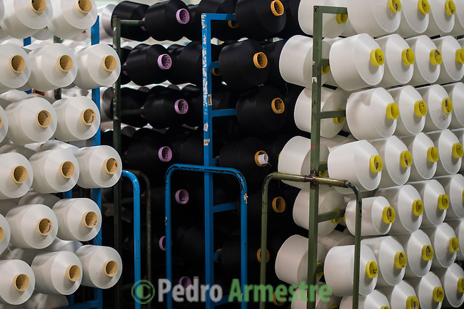 "A picture taken on November 6, 2015 shows spools of yarn made using plastic waste at a yarn processing plant in Angles, north-eastern Spain . Ecoalf, a Spanish Madrid-based firm founded in 2010, has already launched ""a new generation"" of clothes and accessories made from plastic bottles, old fishing nets and used tires found on land.  © Pedro ARMESTRE"
