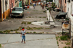 A boy in a carnval mask runs up Curuguaty street in Montevideo, Uruguay prior to the start of the Carnaval parade.