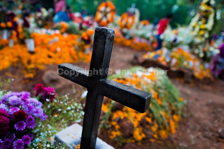 A black cross is seen at the flower-decorated grave during the Day of the Dead festivities in Tzurumútaro, Michoacán, Mexico, 3 November 2014. Day of the Dead ('Día de Muertos') is a syncretic religious holiday, celebrated throughout Mexico, combining the death veneration rituals of the ancient Aztec culture with the Catholic practice. Based on the belief that the souls of the departed may come back to this world on that day, people gather on the gravesites praying, drinking and playing music, to joyfully remember friends or family members who have died and to support their souls on the spiritual journey.