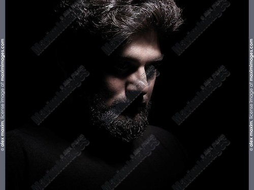 Dramatic shadowy portrait of a thoughful man isolated on black background