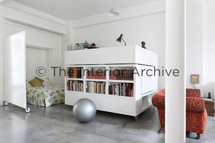 A folding bed and a study on wheels increases the available floor space in the open plan living area