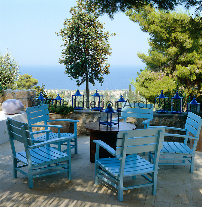 A group of pale blue wooden garden chairs on a shaded terrace with dark blue lanterns on a low wall overlooking the sea