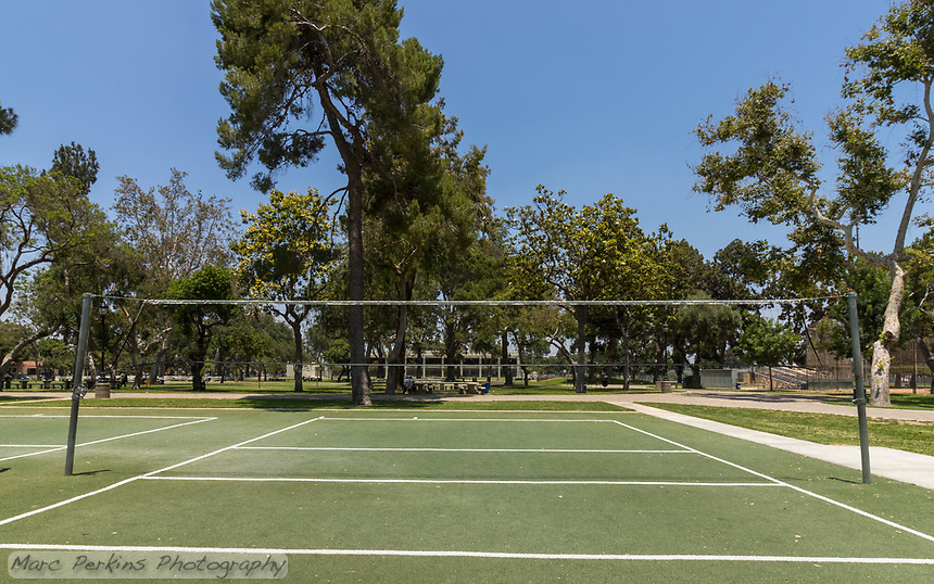 A mid-court view of one of the artificial turf volleyball courts at South Gate Park.  Mature trees tower in the distance under a clear blue sky.