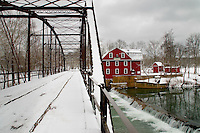 Winter at the War Eagle Mill. War Eagle Mill is a working gristmill in Benton County, Arkansas. A mill has been located on the site as early as 1832, but was destroyed three times, and last rebuilt in 1973. The mill currently the only operating mill in Arkansas and operates as an undershot gristmill, and houses a store and the Bean Palace restaurant. The mill is home to the War Eagle mill Crafts Fair in May and October.  The historic War Eagle Bridge next to the mill is a one lane steel bridge built in 1907 and is listed on the National Register of Historic Places.  The bridge was restored, preserving the historic intergrety in 2010. The mill is located approximately 10 miles east of the city of Rogers in War Eagle, Arkansas.
