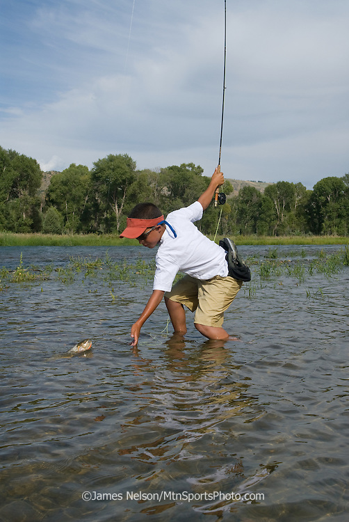 A 10-year-old boy brings a cutthroat trout to hand during a summer day on the South Fork of the Snake River, Idaho.