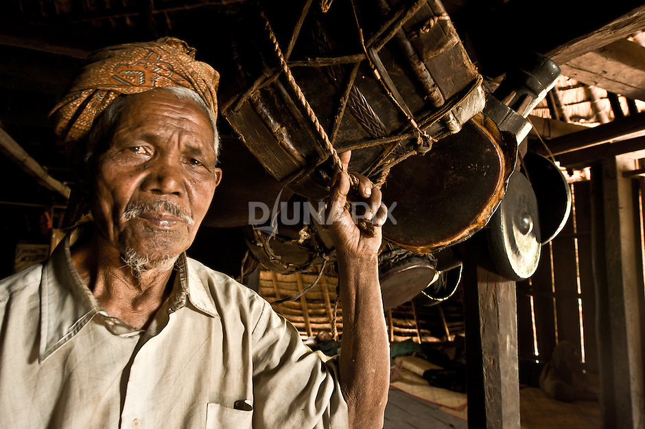 Old man and drums inside tradtional home, Wae Rebo, Flores .