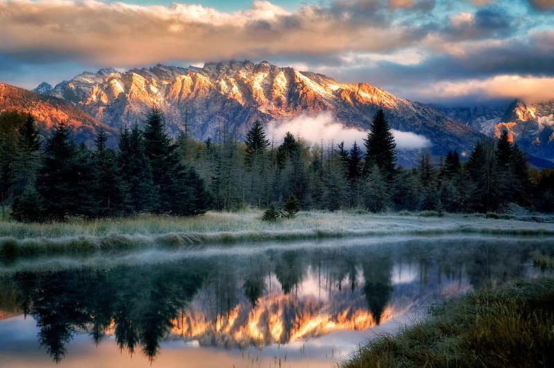 Teton Mountains at sunrise reflected in backwater of Snake River. Grand Teton National Park, Wyoming