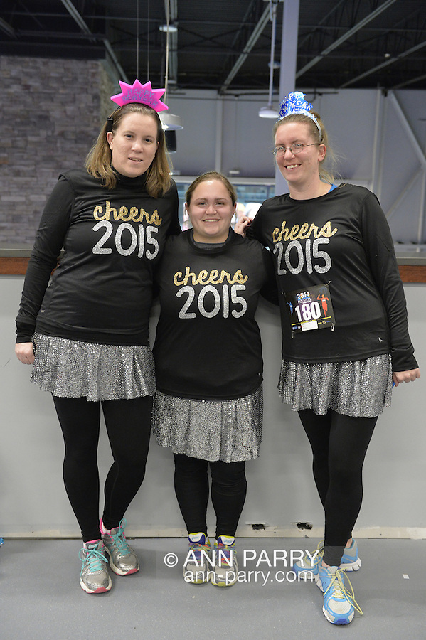 """East Meadow, New York, USA. December 31, 2014. L-R, HEATHER SOFTY of Bethpage, friend CHRISTINA PIETRAS, of Westbury, and sister LAURA SOFTY, of Bethpage, are wearing race bib identification and sparkly black shirts that say """"cheers 2015"""" before participating in a 5K New Year's Eve DASH to support the Long Island Council on Alcoholism and Drug Dependence (LICADD) at the Twin RInks Ice Center at Eisenhower Park in Long Island. The Softy sister are members of Greater Longg Island Running Club (GLIRC). A Skatin' New Year's Eve event started hours earlier and a New Year's Eve Party, open to runners, family and friends continued until 2:30 a.m."""