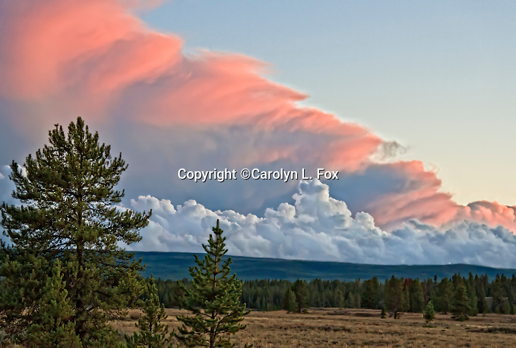 Pink, white and gray clouds roll over the Yellowstone landscape.