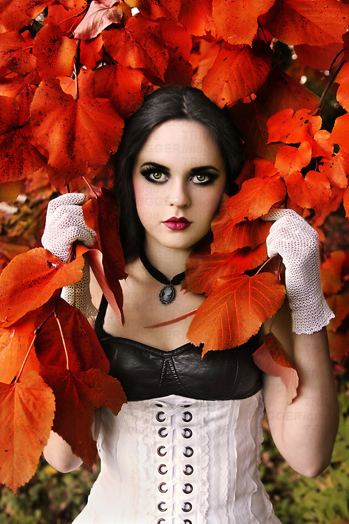 A girl with pale skin and black hair, wearing a white corset and gloves, standing in front a tree in autumn colors and looking at the camera.