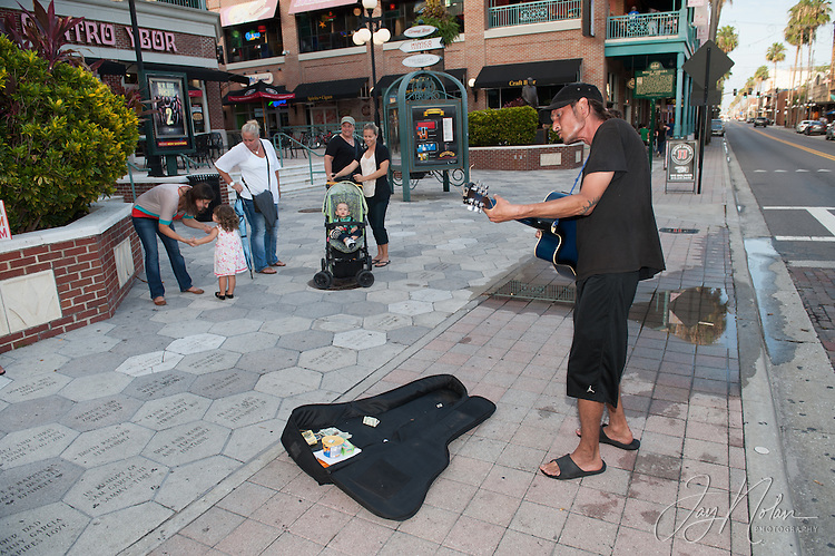 Chad White (Note: Non-Cuban) plays his guitar for cash and/or coins along 7th Avenue in Ybor City today, Thursday 6/11/15. Photo/Jay Nolan