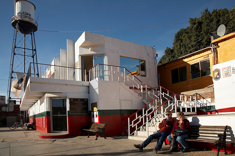 Tourists relaxing on a bench in the central square near the tourist police office, Los Algodones, B.C, Mexico.