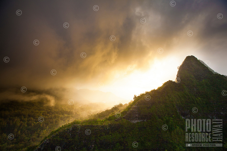 Clouds swirl into the sunset behind the Ko'olau Mountains near the Nu'uanu Pali area on O'ahu.