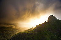 Clouds swirl into the sunset behind the Ko'olau Mountains near the Nu'uanu Pali area on O'ahu.