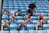 A member of staff lays out cardboard cut outs of Millwall fans in the stand during Millwall vs Swansea City, Sky Bet EFL Championship Football at The Den on 30th June 2020