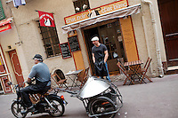 A neighbour and maker of local speciality food 'socca' that he delivers by motorbike passes in front of restaurant 'Chat Noir, Chat Blanc', Nice, France, 10 April 2012