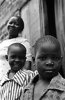 Many children have lost one or both of their parents to HIV/AIDS. Although there is still a significant male population and many husbands and fathers work, there is still an enormous loss of male presence in Uganda.  Many men have perished from HIV/AIDS, thus obligating women to become an even more relevant force in the social fiber of the country. If both parents have died, in many cases, a member of the extended family will take the responsibility of parenting the child (children), even under the strict suppression of poverty. Pictured here, this single mother takes care of her child. One of every six children in Uganda is an orphan, equaling significantly over one million. Bugembe, Jinja District, Uganda, Africa. June 2004 © Stephen Blake Farrington