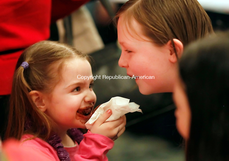 Southbury, CT-12 February 2012-021212CM10-  Abigail Greene, 5,  shares her chocolate cupcake from Sweet-Maria's with her sister Hope Greene, 12, both of Waterbury during the 19th annual Chocolate Lovers' Expo to benefit Easter Seals, at the Crowne Plaza Hotel Sunday afternoon in Southbury.   Christopher Massa Republican-American