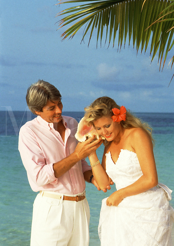 Couple in white listening to conch shell on beach