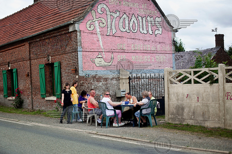 Local people have a meal together as they wait see the Tour de France cycling competition pass through their village.