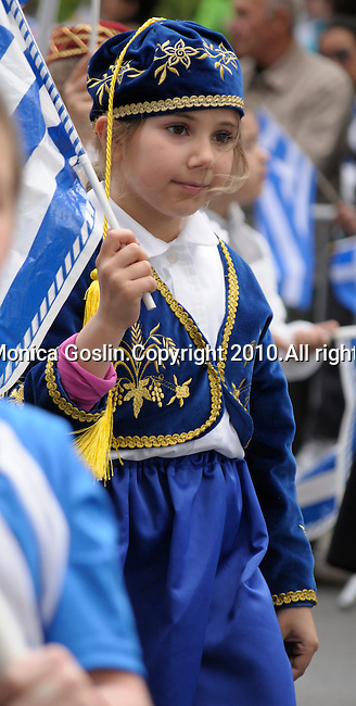 Greek Parade in New York City. A girl in a costume and holding a Greek flag in the Greek Parade in New York City.