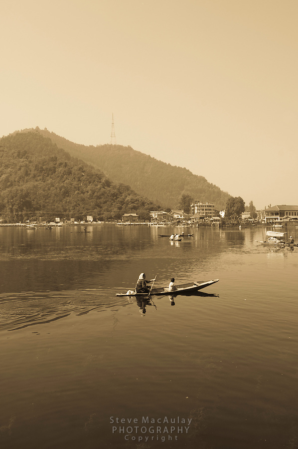 Mother and son paddling traditional shikara on Dal Lake, Srinagar, Kashmir, India.