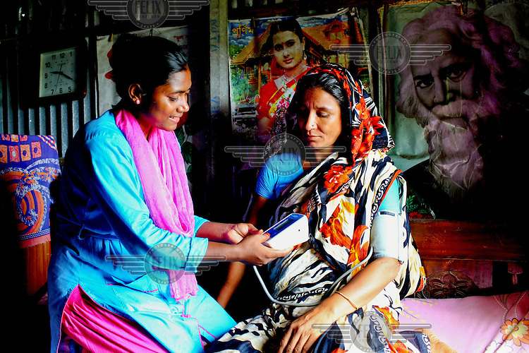 Info Lady Mahfuza measures the blood pressure of an client. In rural Bangladesh the Info Ladies are bringing internet services to men and women who need information but don't have the means to access the web. After three months of training the Info Ladies set out each day in their pink and blue uniforms to cycle to remote villages where they provide Skype connections to villagers who want to communicate with relatives working overseas. They also provide tech services, photographs, health tests, cosmetics and other small items that can be easily carried.
