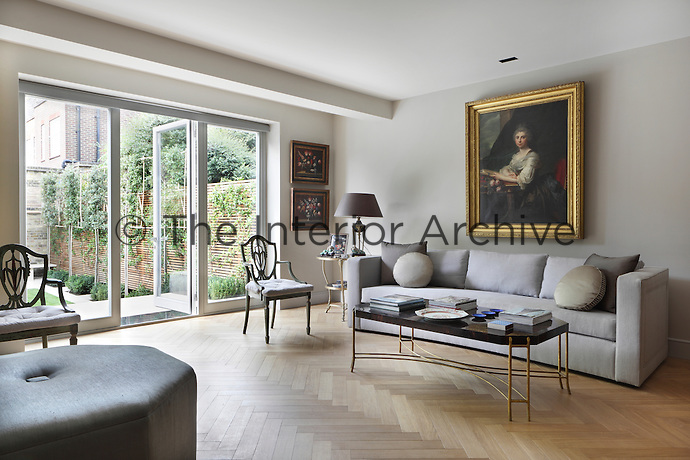 Parquet flooring, antique furniture and paintings compliment this neutrally coloured spacious, contemporary living area