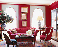In the elegant sitting room the custom-made sofa and throw pillows are covered in a Clarence House linen and velvet respectively and the bold colour perfectly matches the red felt walls. The windows are dressed in Kravet silk and the trio of artworks in between the windows is by Jean-Louis Forain. The room is furnished with a number of antique pieces such as the Oushak rug and the cocktail table.