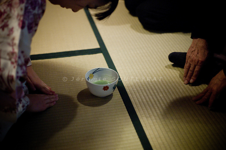 Tokyo, October 24 2010 - Tea ceremony in Taishakuten temple, Shimabata. A young japanese girl bows in front of a guest after serving his cup of tea.