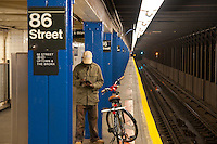 Man with the bike in New York subway station waiting for the train