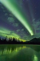 Green bands of northern lights, aurora borealis over a frozen lake, Brooks Range, Arctic, Alaska
