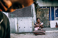 Jolin, 35, plays the Ukulele on the street of North Camp, one of the most populated slums on Ebeye.