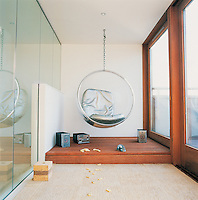 An Eero Aarnio bubble chair hangs from the ceiling of a garden room of a penthouse apartment. The floor to ceiling windows allow plenty of light into the room, which has special acoustics to reduce the hum of the city noise below.
